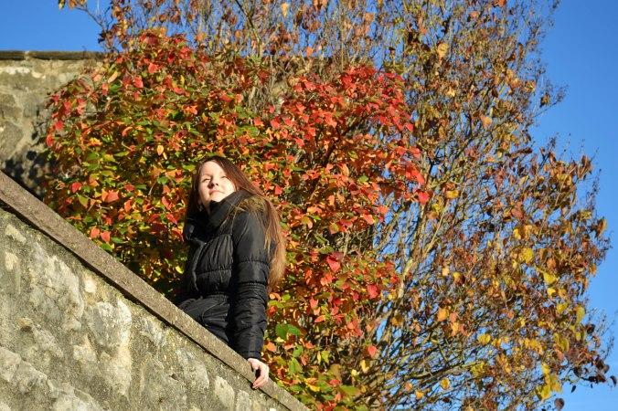 Das ist übrigens meine beste Freundin, die in Warburg auf einer Mauer umringt von Herbstblättern ist.